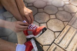 runner tying shoes, good running shoes and gear