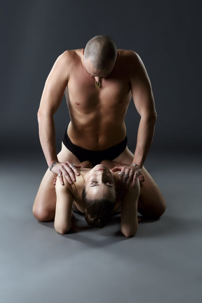 Nude couple yoga. Man on top of woman