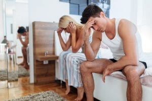 couple in bed having problems, stressed