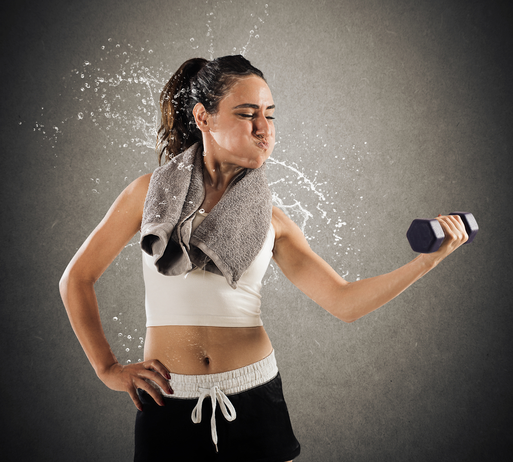 sweating woman lifting dumbbell