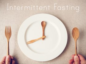 wooden spoon and fork as clock hands on plate for intermittent fasting