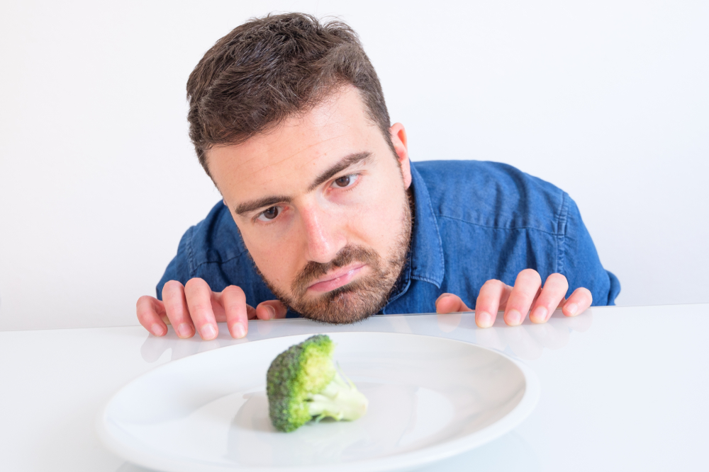 Progentra user looking sadly at lone broccoli on plate