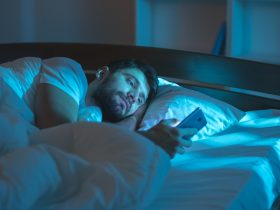 man staying up late at night on his mobile phone reading about Progentra and its benefits