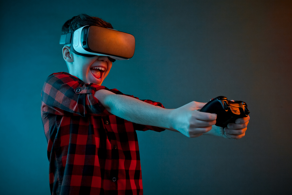 young boy playing video game with VR glasses
