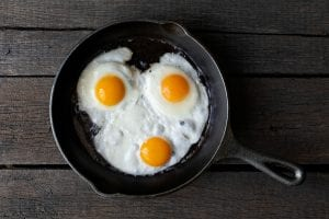 3 fried eggs in cast iron pan