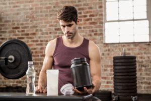 man holding protein shake at gym